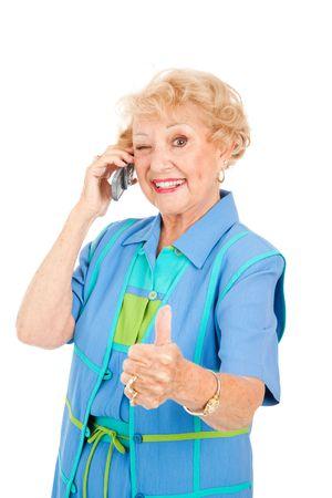 ecoute active: Senior femme sur son t�l�phone portable donne un clin d'oeil et le pouce en l'air pour une bonne r�ception. Banque d'images