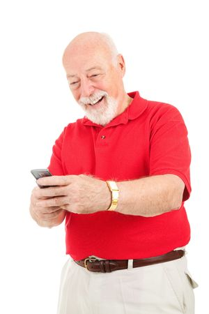 Senior man enjoys text messaging on his cell phone.  Isolated on white.