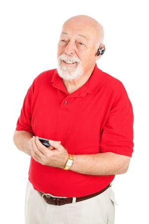 actief luisteren: Senior man met een handsfree-set te spreken op zijn mobiel. Geïsoleerd op wit.