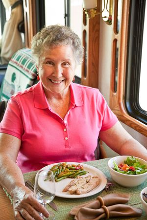 Senior woman having an elegant turkey dinner in her motor home.   Imagens