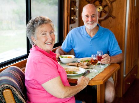 Senior couple enjoys a healthy lunch in the kitchen of their motor home. Focus on the wife.  photo