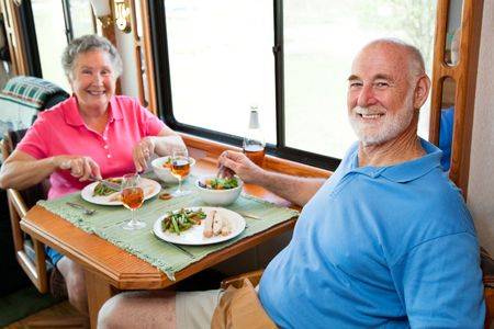 Senior couple enjoying a romantic dinner in their motor home.  Focus on husband in foreground.   photo