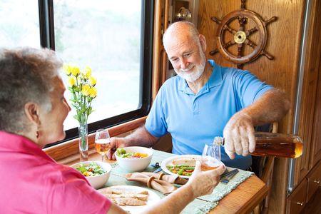Senior couple having romantic dinner in their motor home. photo