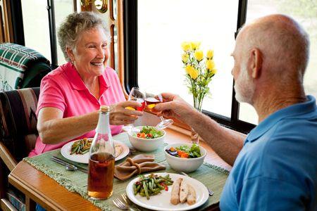 Senior couple enjoying a romantic dinner in their motor home.   photo