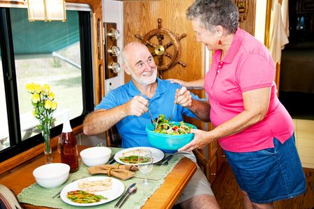 Senior couple enjoying a healthy meal in their luxury motor home.   photo