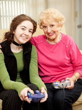 seventy two: Grandmother and teen granddaughter bonding by playing video games together.