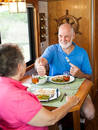 Senior man gives his wife a big thumbs up for the delicious dinner she made in their motor home. photo