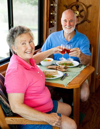 Senior couple enjoys a romantic meal in the kitchen of their motor home.   photo