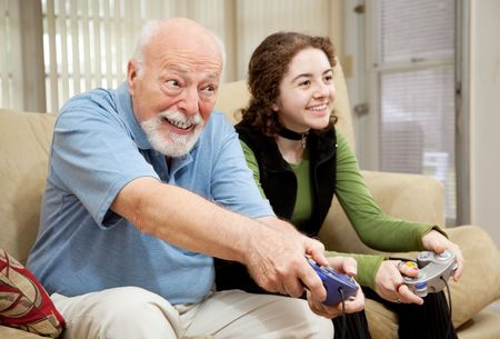 Senior man playing a video game with his teenage granddaughter.   photo
