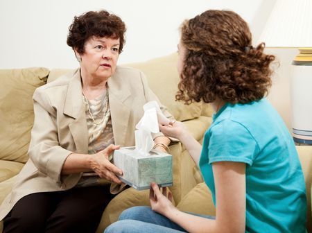Understanding therapist handing tissue box to an upset teen patient.   Stock Photo - 5127770