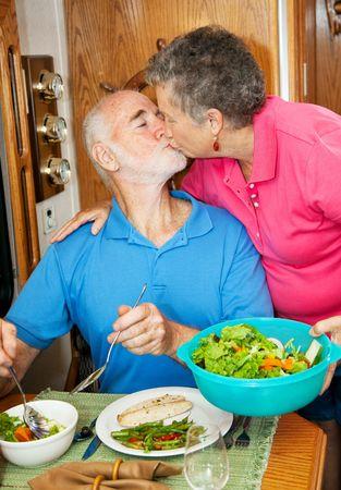 Senior man kisses his wife as she serves him dinner in their motor home.   photo