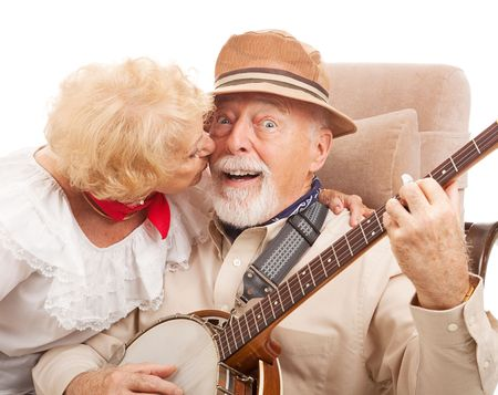 rewarded: Senior man playing banjo for his lady is rewarded with a kiss.