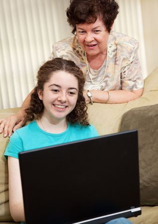 browses: Mom watches as her teen daughter browses the internet.