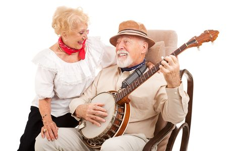 Senior man courts his lady love by playing banjo for her.  Isolated on white.   photo