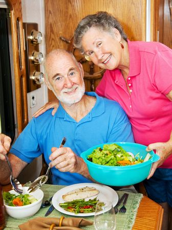 Senior woman serves a healthy dinner to her husband in their modern motor home.   photo