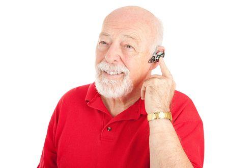 actief luisteren: Senior man met een hands-free mobiele telefoon oor stuk. Geïsoleerd op wit.