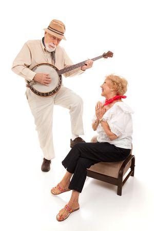 Senior man serenading his lady on his banjo.  Isolated on white. photo