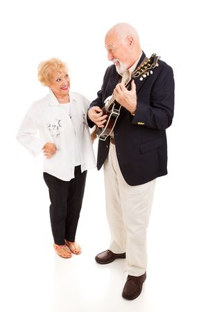 Handsome senior man serenading his beautiful lady on the mandolin.  Full body isolated. photo