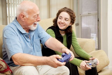 Grandfather spends quality time with his granddaughter playing video games.   photo