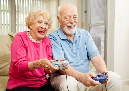 Senior couple has fun at home playing video games together.   Imagens