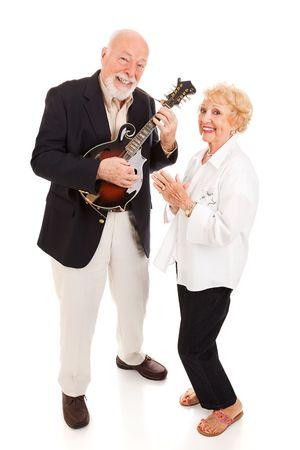 actief luisteren: Senior man speelt mandoline, terwijl zijn vrouw zingt mee. Volledige lichaam geïsoleerd.