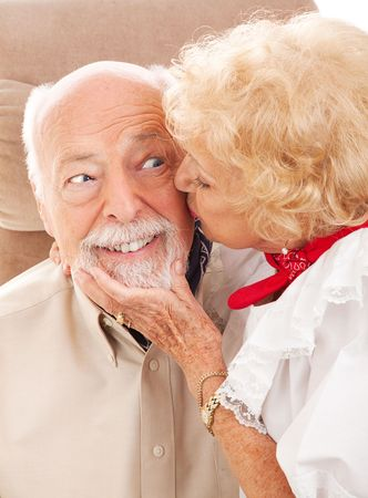 sweetie: Happy senior man gets a kiss from his sweetie.   Stock Photo
