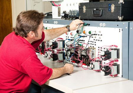 are industrial: Teacher or adult student working on an industrial motor control panel trainer.
