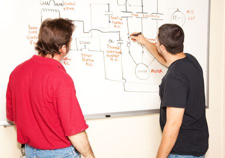 Electrical engineering student draws a diagram of a circuit on the white board while teacher looks on.