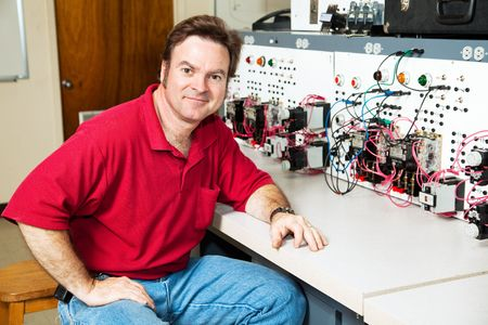 Electrical engineering teacher sitting at an industrial motor control center in his classroom.   photo