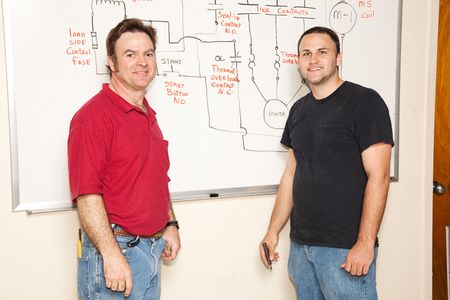 Engineering student and teacher going over electrical schematic on the board.   photo