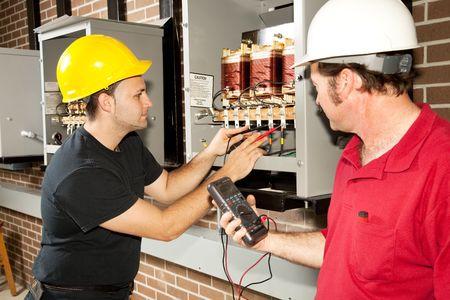 Elektriciens werken op een industriële macht distributie centrum. Werkelijke elektriciens en authentieke nauwkeurige inhoud. Stockfoto