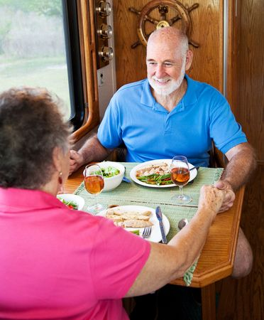 Senior couple enjoys conversation over a healthy meal in their motor home.   photo