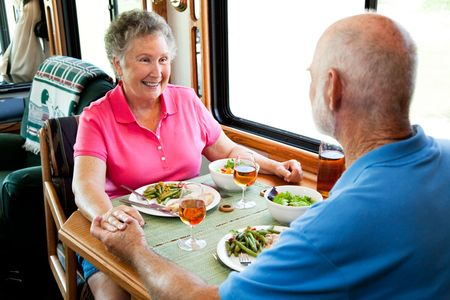 Senior couple holding hands about to eat a healthy meal in their motor home. photo