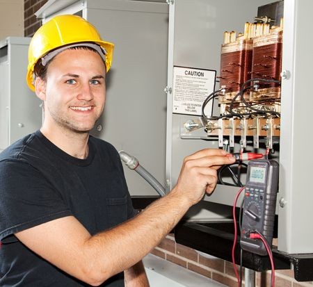Young apprentice electrician measures power coming through coils of an industrial power distribution center.