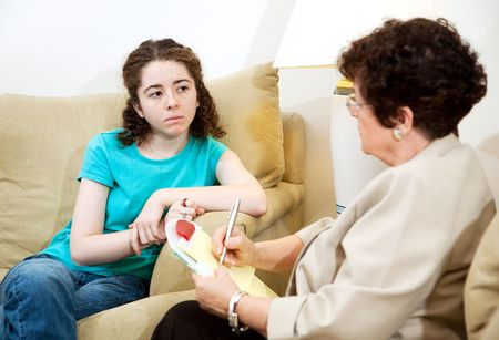 Depressed teen girl consulting with a psychologist.   Stock Photo