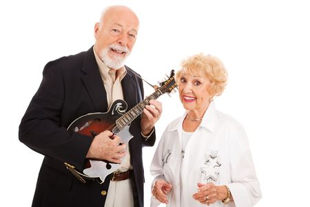 Musical senior couple.  He plays mandolin and she sings along.  Isolated on white.   photo