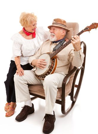 Senior man serenades his beautiful wife on the banjo.  Isolated on white. photo