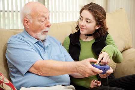 seventy two: Teen girl teaching her grandfather how to play video games.