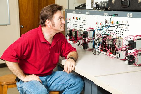 Engineer sitting at an electrical motor control panel.   photo
