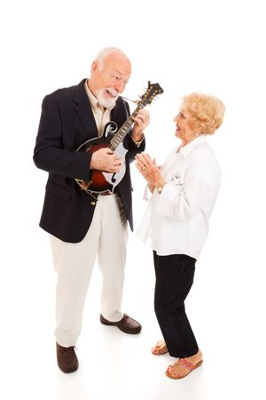 Senior man plays mandolin while his wife signs along.  Full body isolated. photo