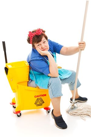 Tired unhappy cleaning lady sitting in her mop bucket.  Isolated on white. photo