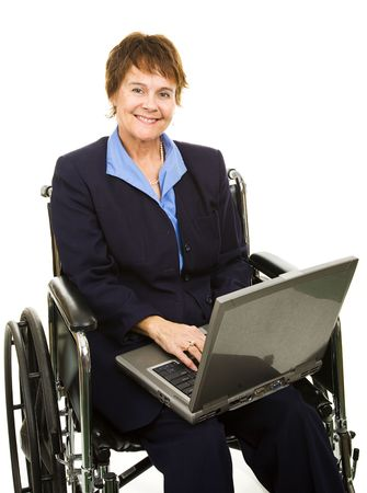 Pretty, smiling businesswoman in a wheelchair working on her laptop computer.  Isolated. photo