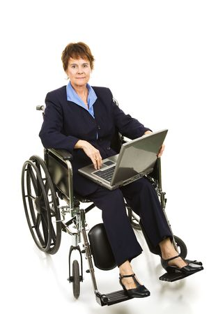 Serious buisinesswoman in a wheelchair working on her laptop computer.  Isolated on white. photo