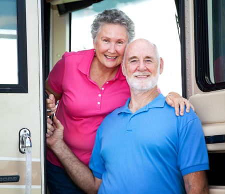Portrait of senior couple at the door of their luxury RV. 스톡 콘텐츠