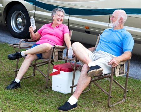 Senior campers sitting in folding chairs outside their motor home.   photo