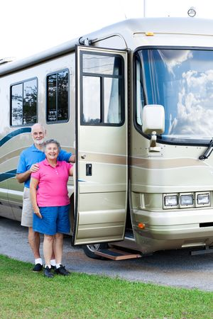 beside: Happy retired couple standing beside their luxury motor home.   Stock Photo