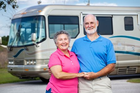 active holiday: Active retired couple in love with their luxury motor home in background.