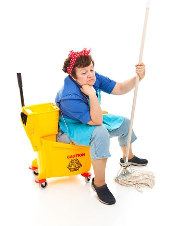 Depressed maid sitting in her bucket and holding her mop, with a sad expression on her face.  Full body isolated.
