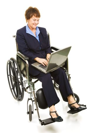 Disabled businesswoman smiles as she types on her laptop computer.  Full body isolated on white.