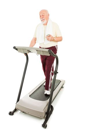 Senior man enjoys music on his mp3 player while he walks on the treadmill.  Full body isolated on white. photo